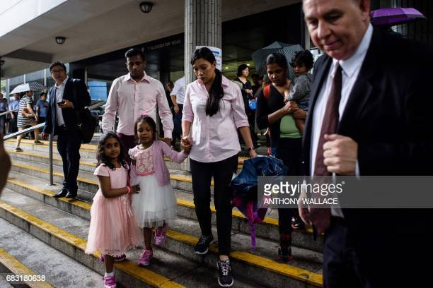 Lawyer Robert Tibbo and his clients Sri Lankan refugee Ajith Puspa Nadeeka holding her son Danath and Filipino refugee Vanessa Rodel with her...