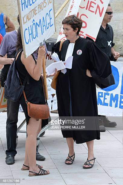 A lawyer wearing the robe gives leaflets to protesters in front of the High Court of Bordeaux southwestern France on June 26 2014 as French artists...