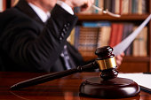 Lawyer working, holding Law document with judge's gavel at desk in courtroom lawyer office, tribunal and justice concept