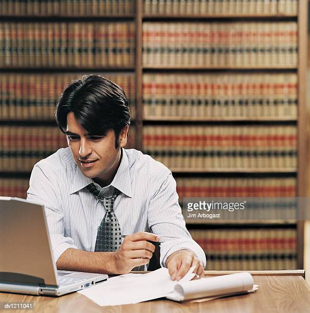 Lawyer Working in a Library and Using a Laptop