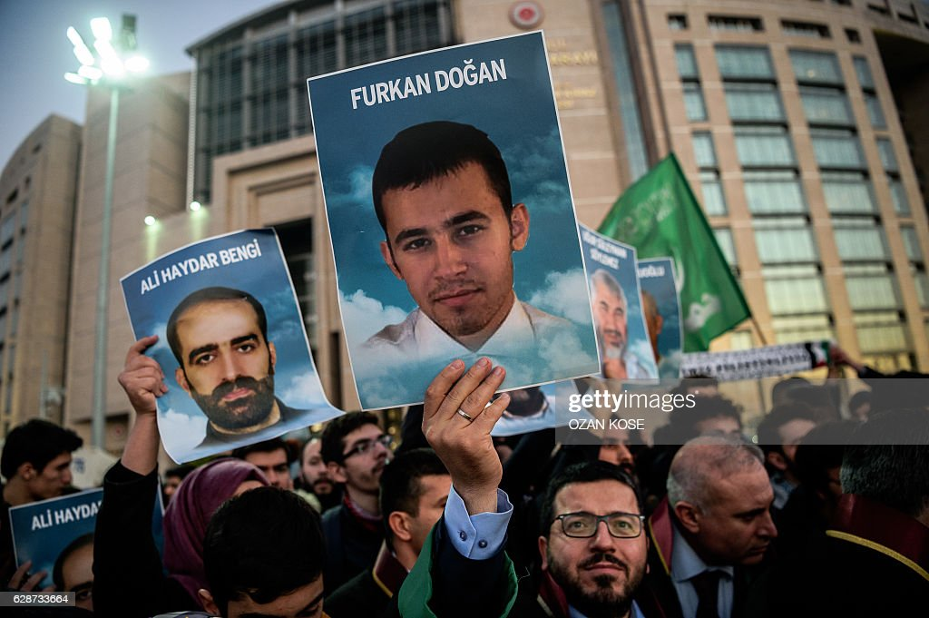 Lawyers and families hold pictures of victims and shout slogans on December 9, 2016 outside the Istanbul courthouse as Turkish court is expected to rule in the case of Israelis charged in absentia over a deadly commando raid on a Gaza-bound aid ship in 2010. Nine Turks died when Israeli marines stormed the 'Mavi Marmara', which was part of an aid flotilla to break a naval blockade of the Gaza Strip. One more died in hospital in 2014. Ties between Israel and Turkey crumbled after the raid but in June 2016 they finally agreed to end the bitter six-year row after months-long secret talks. / AFP / OZAN