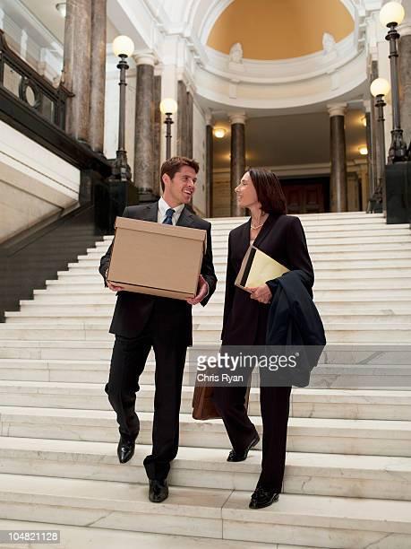 Advogados carregar ficheiros e caixa descer escadas