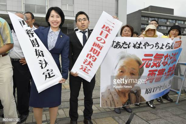 Lawyers for Ayako Haraguchi hold banners celebrating a Kagoshima District Court decision on June 28 to retry their client who served a 10year prison...