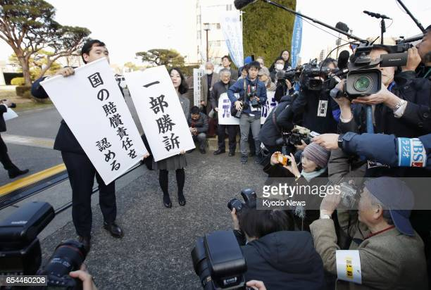 Lawyers for plaintiffs hold banners on March 17 in front of the Maebashi District Court north of Tokyo after it ruled negligence by the central...
