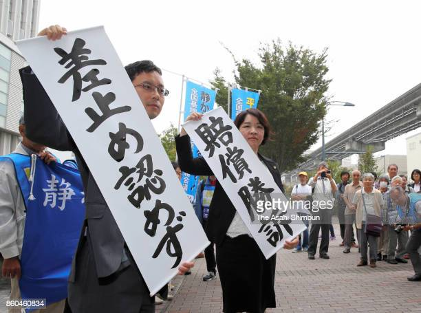 Lawyers for the plaintiffs hold up banners describing the Oct 11 ruling on noise pollution at Yokota Air Base on October 11 2017 in Tachikawa Tokyo...