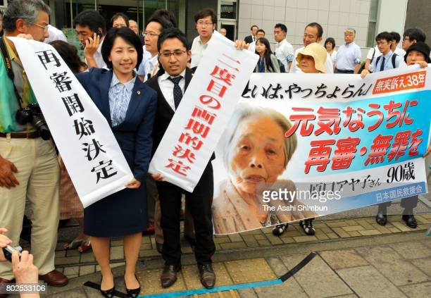 Lawyers hold banners after the Kagoshima District Court approved the retrial for Ayako Haraguchi who was convicted in the 1979 death of her...