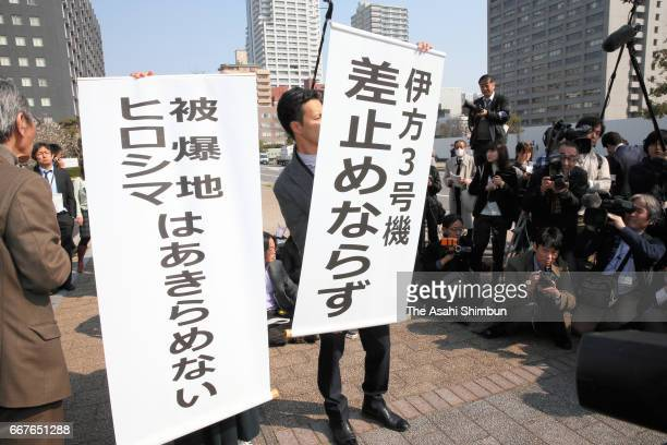 Lawyers hold up signs that say a request for a temporary injunction on the Ikata nuclear plant had been rejected in front of the Hiroshima District...