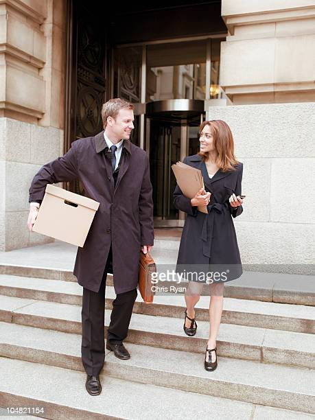 Lawyers leaving courthouse with files and box