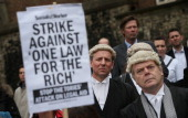 Lawyers listen to speeches near Parliament during a demonstration in support of Legal Aid on May 22 2013 in London England Lawyers are calling on the...