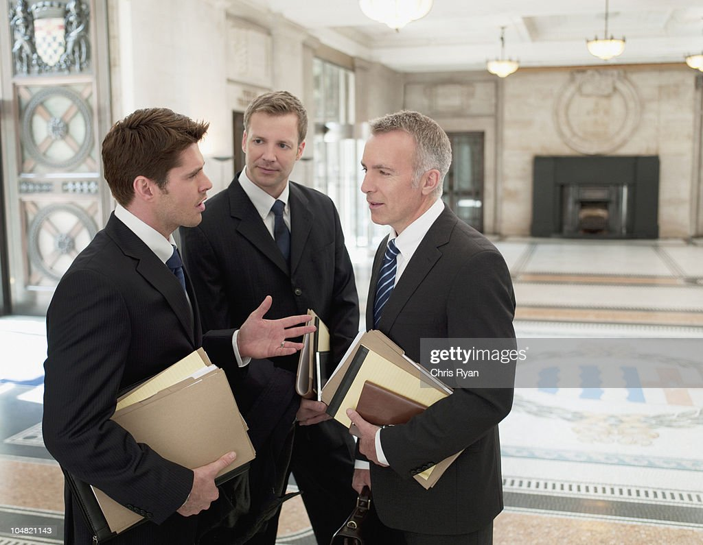 Lawyers with files talking in lobby : Stock Photo