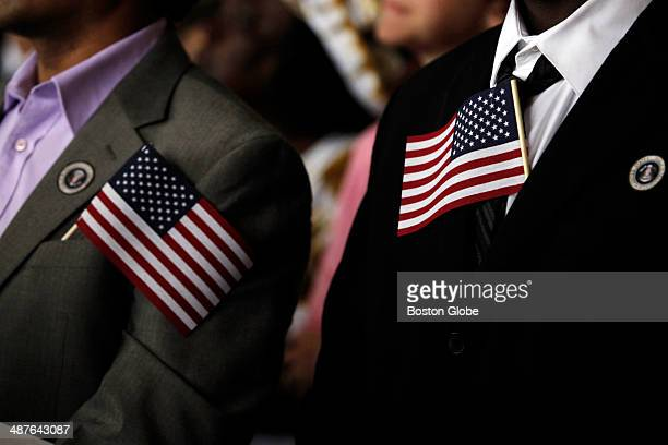 Lax Iyer originally from India left and Jermaine Green originally from Jamaica wear flags in their lapels as they wait to become citizens during a...