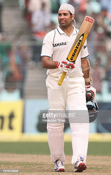 Laxman of India raises his bat after completing his century during the second day of second test match between India and West Indies at Eden Garden...