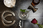 Lay flat overhead of bar countertop with deconstructed elements of Kentucky Derby mint julep with horse shores and red rose.