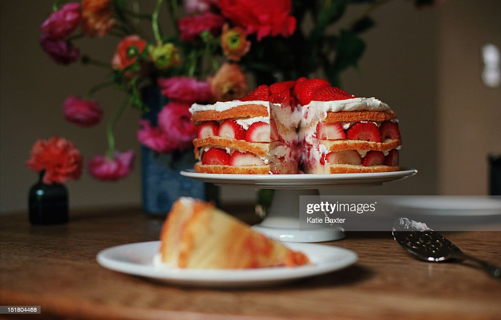 Layered strawberry cake with background flowers : Stock Photo
