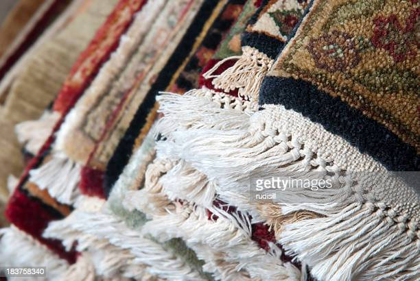 Layers of colorful Persian rugs piled on top of each other