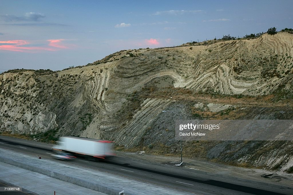 Layers of earthquake-twisted ground are seen at dusk where the 14 freeway crosses the San Andreas Fault on June 28, 2006 near Palmdale, California. Scientists are warning that after more than 300 years with very little slippage, the southern end of the 800-mile-long San Andreas Fault north and east of Los Angeles has built up immense pressure that could trigger a massive earthquake at any time. Such a quake could produce a sudden lateral movement of 23 to 32 feet which would be would be among the largest ever recorded. By comparison, the 1906 earthquake at the northern end of the fault destroyed San Francisco with a movement of no more than about 21 feet. Experts believed that a quake of magnitude-7.6 or greater on the lower San Andreas could kill thousands of people in the Los Angeles area with damages running into the tens of billions of dollars. The San Andreas Fault is the point of collision between the Pacific and the North American tectonic plates of the Earth?s crust.
