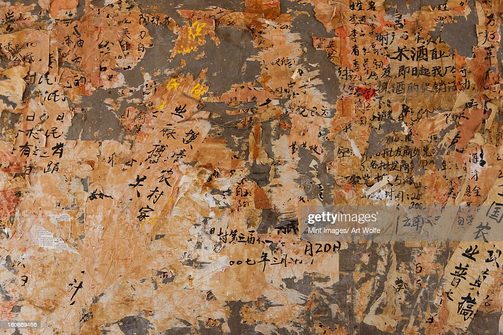 Layers of paper peeling off a wall, Kunming, China : Stock Photo