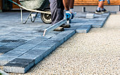 Laying gray concrete paving slabs in house courtyard driveway patio. Professional workers bricklayers are installing new tiles or slabs for driveway, sidewalk or patio on leveled  foundation base made