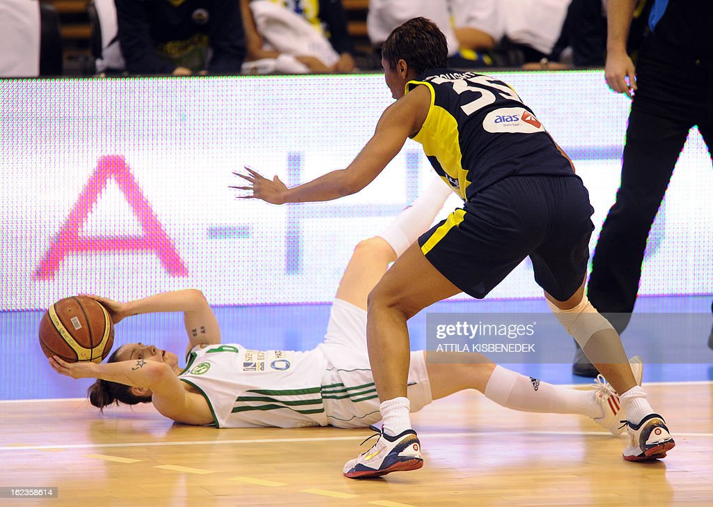 Laying on parquets, Australian Anne Hurst of Hungarian Hat-Agro UNI Gyor passes the ball against U.S. Angel McCoughtry (R) of the Turkish Fenerbahce Istanbul in the local sport hall of Gyor on February 22, 2013 during their Euro League match.