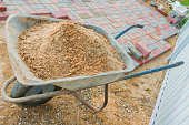 laying red and gray concrete paving blocks. Road Paving, construction. Wheelbarrow full of sand