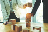 Shot of two unrecognisable businesspeople stacking wooden blocks together in an office