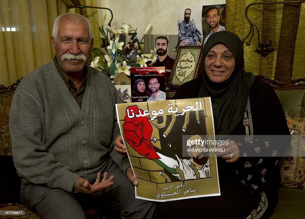 Layla (R) and Tareq Issawi hold a poster of their son Samer, who has been on hunger strike for 260 days while being held in an Israeli prison, as they celebrate a deal for his release at their home in the East Jerusalem neighbourhood of Issawiya on April 23, 2013. Issawi has agreed to end his protest in return for his release, his lawyer said.