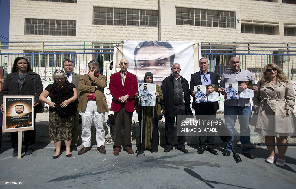 Layla Issawi (C) holds a picture of her son Samer Issawi, a Palestinian held in Israeli jail and on hunger strike for more than 200 days, alongside her husband Tareq (C-R) and European politicians of the Council for European Palestinian Relations (L to R) Sandra White and Jim Hume from Scotland, Niccolo Rinaldi from Italy, Gerald Kaufman of Britain, Pat Sheehan of Ireland and Pauline McNeill of Scotland on March 2, 2013. The European lawmakers were in the region in a show of support for Palestinian detainees on hunger strike in Israeli prisons. AFP PHOTO/AHMAD GHARABLI