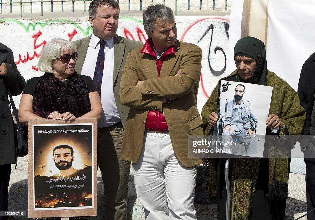 Layla Issawi (R) holds a picture of her son Samer Issawi, a Palestinian held in Israeli jail and on hunger strike for more than 200 days, alongside European politicians of the Council for European Palestinian Relations (L to R) Niccolo Rinaldi from Italy, Jim Hume and Sandra White from Scotland, on March 2, 2013. The European lawmakers were in the region in a show of support for Palestinian detainees on hunger strike in Israeli prisons. AFP PHOTO/AHMAD GHARABLI