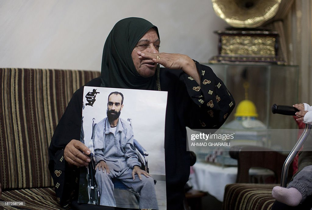 Layla Issawi holds a picture of her son Samer who has been on hunger strike for 260 days while being held in an Israeli prison, as she celebrates a deal for his release at their home in the East Jerusalem neighbourhood of Issawiya on April 23, 2013. Issawi has agreed to end his protest in return for his release, his lawyer said. AFP PHOTO/AHMAD GHARABLI
