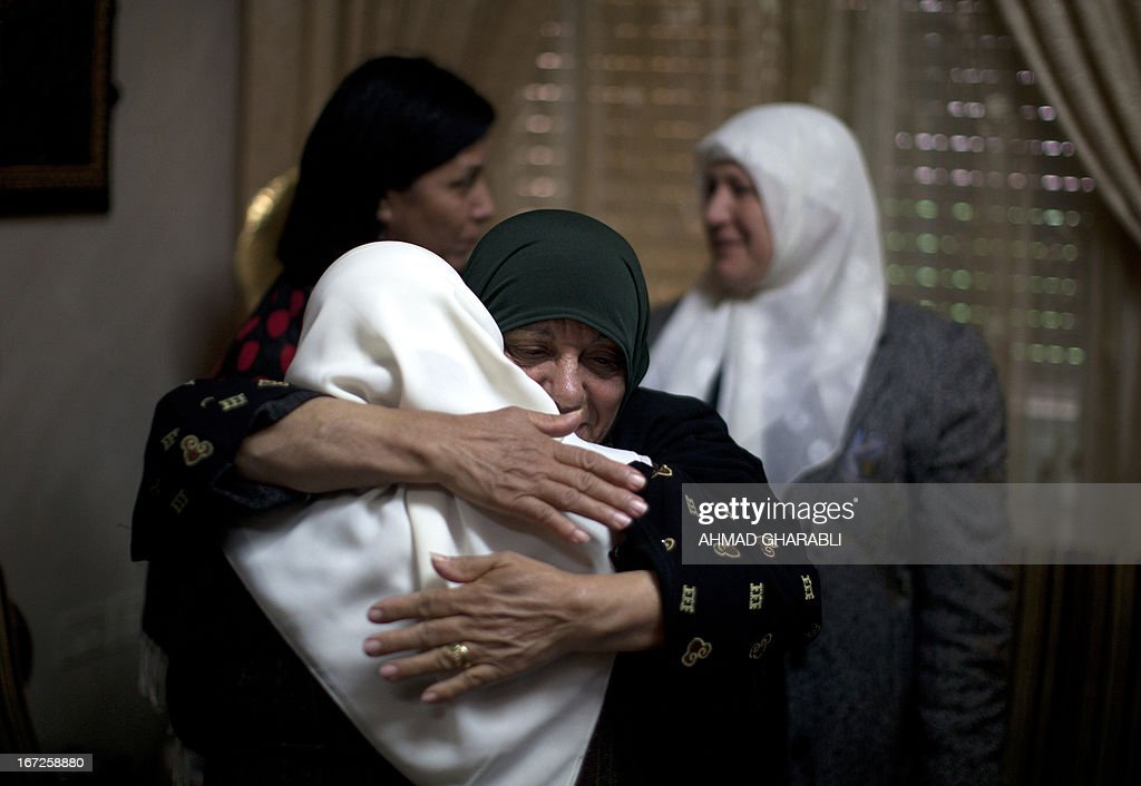 Layla Issawi (C-back) hugs a relative as they celebrate a deal for the release of her son Samer who has been on hunger strike for 260 days while being held in an Israeli prison, at her home in the East Jerusalem neighbourhood of Issawiya on April 23, 2013. Issawi has agreed to end his protest in return for his release, his lawyer said. AFP PHOTO/AHMAD GHARABLI