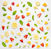 Flat lay of chaotic seamless background with slices of fresh citrus and strawberry in composition with banana and mint leaves.