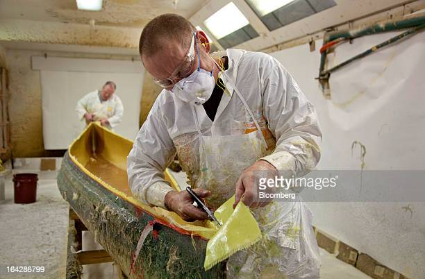 Layup supervisor Roy Pelowski cuts Kevlar fabric in a mold used to make a Prism canoe at the Wenonah Canoe factory in Winona Minnesota US on Thursday...
