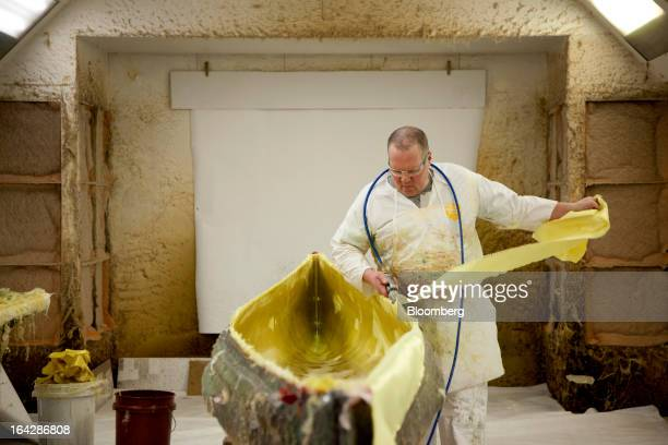 Layup technician Richard Carpenter cuts Kevlar fabric used to form a Prism canoe in a mold at the Wenonah Canoe factory in Winona Minnesota US on...