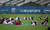 Layvin Kurzawa of PSG and teammates stretch foliowing the first training session of the season for Paris SaintGermain at PSG training camp Centre...