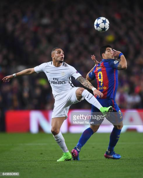 Layvin Kurzawa of PSG battles with Luis Suarez of Barcelona during the UEFA Champions League Round of 16 second leg match between FC Barcelona and...