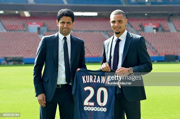 Layvin Kurzawa poses with his new jersey next to Nasser AlKhelaifi President of PSG during his presentation to the media at Parc des Princes on...