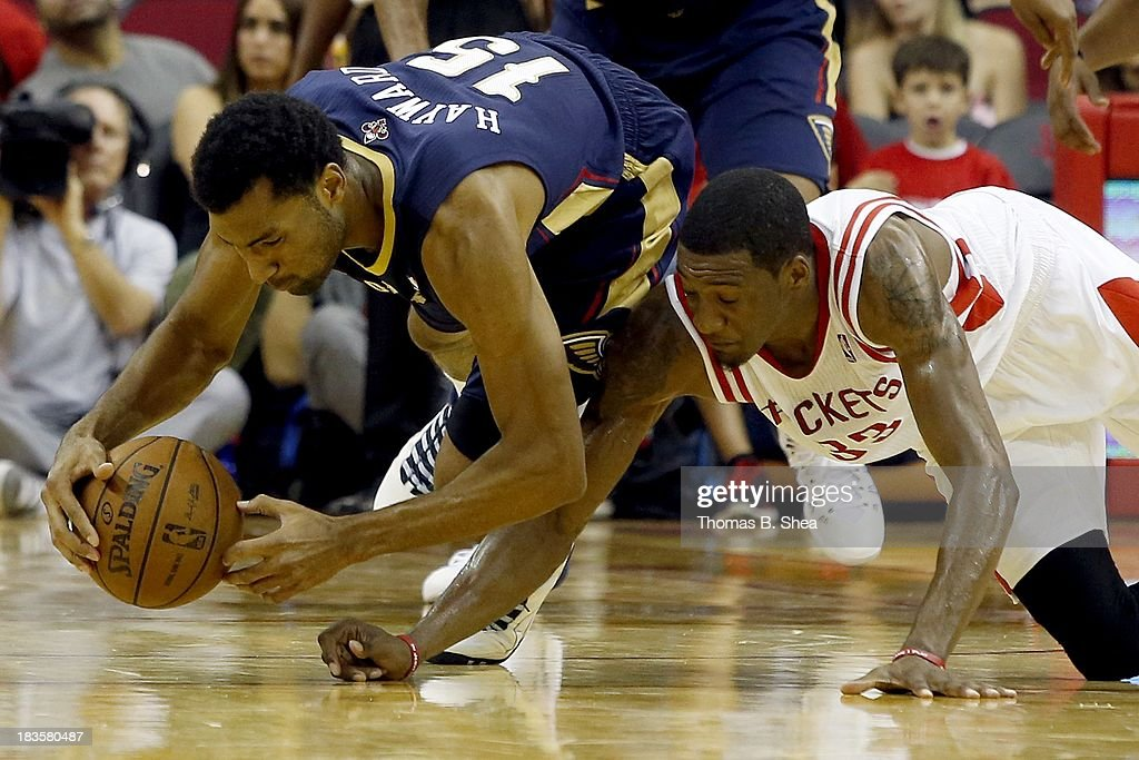 Lazar Hayward #15 of the New Orleans Pelicans fights for a loose ball against Robert Covington #33 of the Houston Rockets in a preseason NBA game on October 5, 2013 at Toyota Center in Houston, Texas. The Pelicans won 116 to 115.