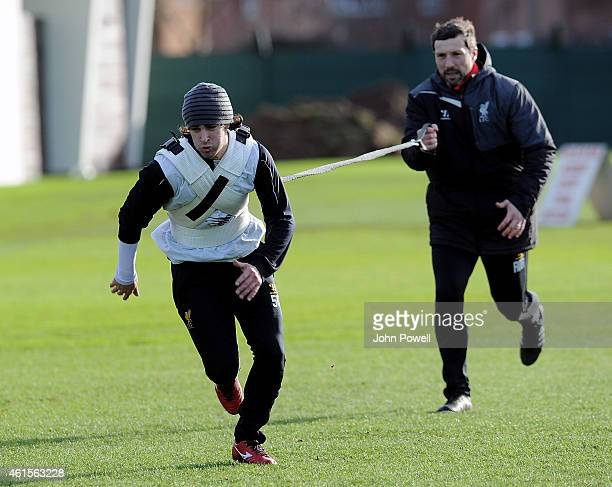 Lazar Markovic of Liverpool with Ryland Morgans head of fitness in action during a training session at Melwood Training Ground on January 15 2015 in...