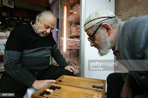 Lazari Kozmaoglu left Istanbul's last pork butcher plays backgammon with a friend in his shop in Istanbul Turkey on Thursday March 6 2008 Kozmaoglu...