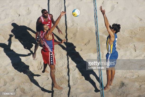 Lazaro Milian Carvajal of Cuba blocks against Adriano Garrido of Brazil as Cuban team mate Ihosvany Chambers Hernandez looks on during their Beach...