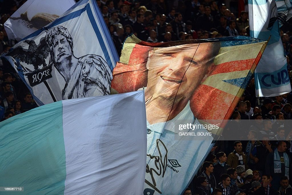 Lazio' fans wave banners with the portrait of Lazio former English soccer player Paul Gascoigne prior the Italian Serie A football derby between AS Roma and Lazio Rome on April 07, 2013 at the Olympic stadium in Rome.