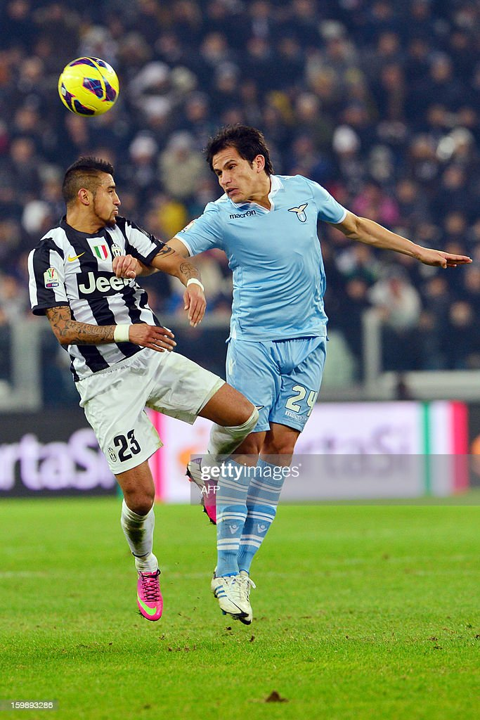 Lazio's Argentinian midfielder Cristian Ledesma (R) challanges for the ball with Juventus' midfielder of Chile Arturo Vidal during their TIM CUP football match at the Juventus Stadium in Turin on January 22, 2013. AFP PHOTO / GIUSEPPE CACACE