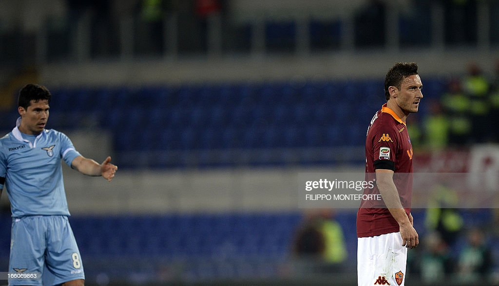 Lazio's Brazilian midfielder Anderson Hernanes (L) gestures against AS Roma forward Francesco Totti during the Italian Serie A football derby between AS Roma and Lazio on April 8, 2013 at the Olympic stadium in Rome. AFP PHOTO / FILIPPO MONTEFORTE