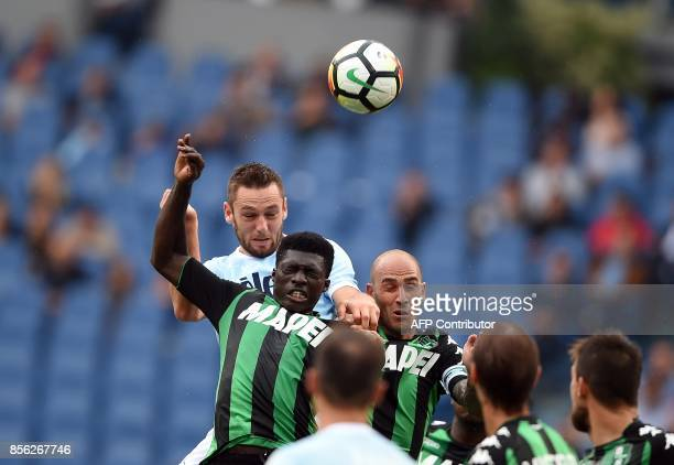 Lazio's defender from Netherlands Stefan de Vrij jumps for the ball with Sassuolo midfielder Alfred Duncan and defender Paolo Cannavaro during the...