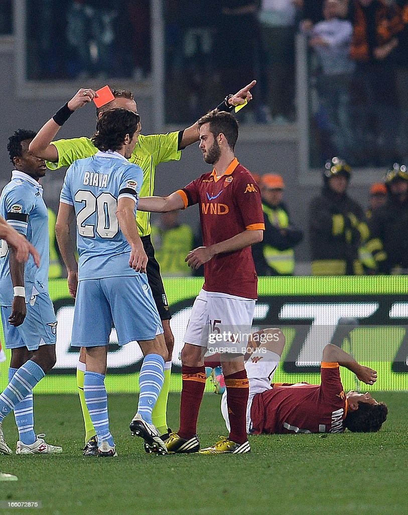 Lazio's defender Giuseppe Biava (L) receives a red card during the Italian Serie A football derby between AS Roma and Lazio Rome on April 8, 2013 at the Olympic stadium in Rome. AFP PHOTO / GABRIEL BOUYS