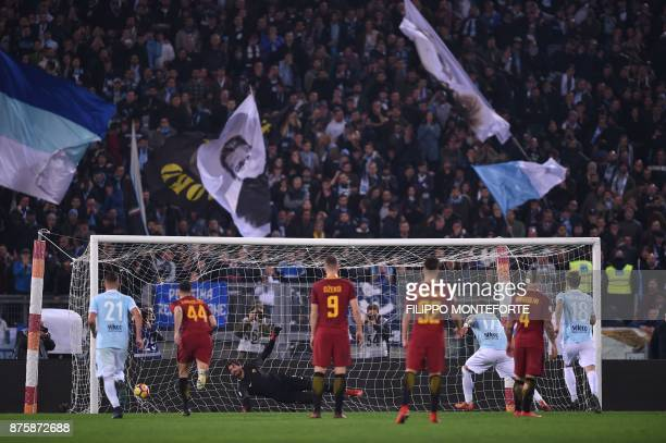 Lazio's midfielder Ciro Immobile scores a penalty against Roma's Brazilian goalkeeper Alisson during the Italian Serie A football match AS Roma vs...
