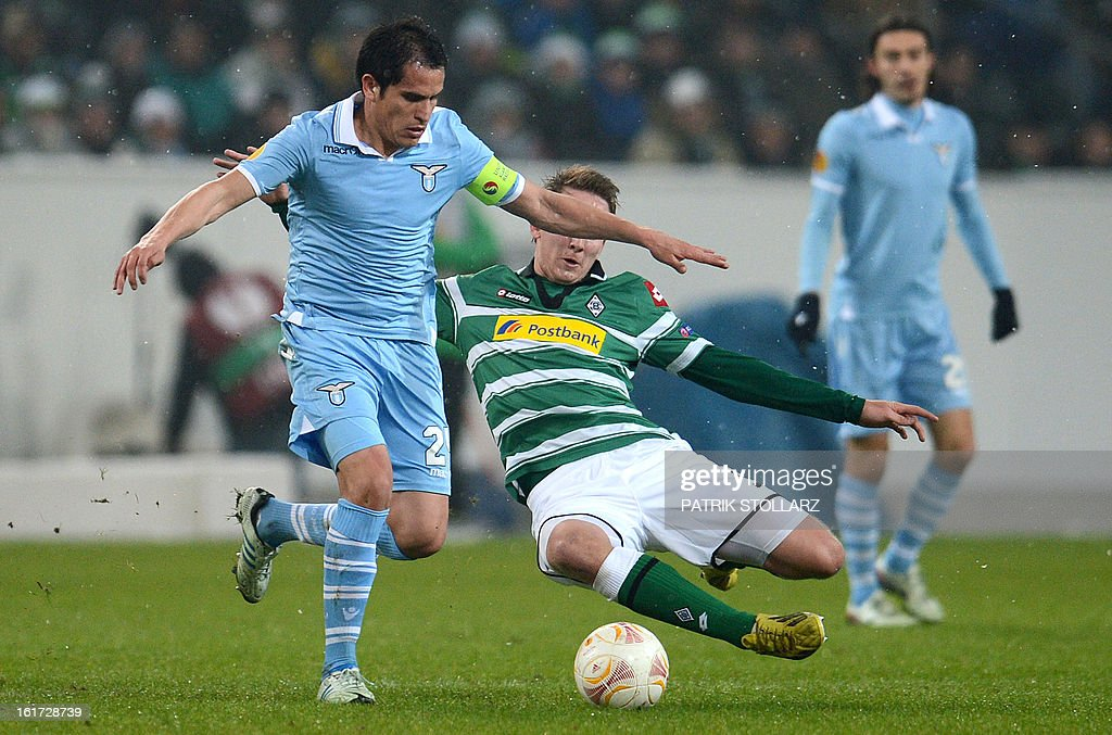 Lazio's midfielder Cristian Ledesma (L) and Moenchengladbach's Dutch forward Luuk de Jong vie for the ball during the UEFA Europa League football match VfL Borussia Moenchengladbach vs SS Lazio on February 14, 2013 in Moenchengladbach, western Germany. AFP PHOTO / PATRIK STOLLARZ