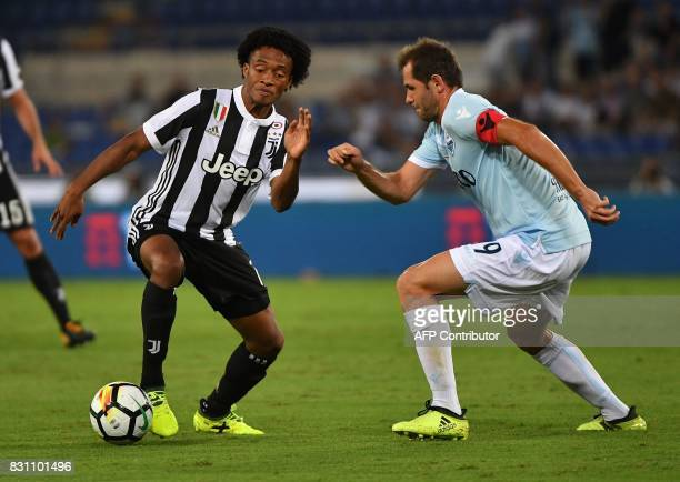 Lazio's midfielder from BosniaHerzegovina Senad Lulic fights for the ball with Juventus's midfielder from Colombia Juan Cuadrado during the Italian...