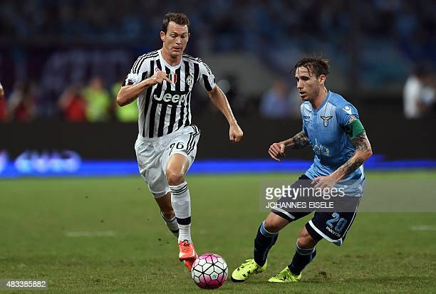 Lazio's midfielder Lucas Biglia and Juventus defender Stephan Lichtsteiner vie for the ball during the Italian Super Cup final football match between...