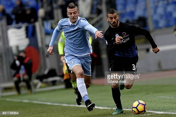 Lazio's Serbian midfielder Sergej MilinkovicSavic fights for the ball with Atalantas Italian Leonardo Spinazzola during the Serie A football match...